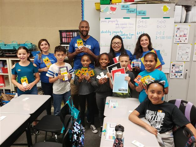 Intel volunteer with donated school supplies and students